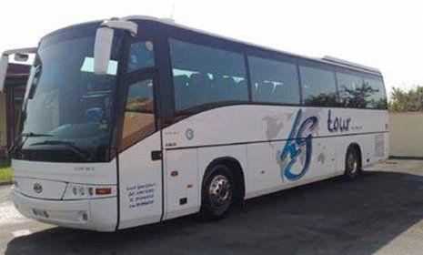 un pullman bianco con vetri fume' con scritto LG Tour in blu e nero