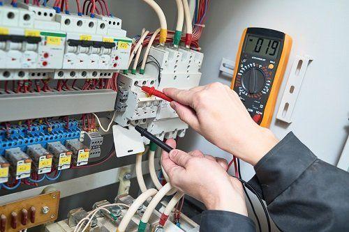 due mani con due tester in un quadro elettrico