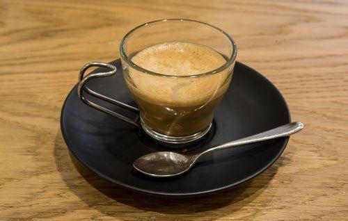 una tazzina di caffè' in vetro con sotto un piattino