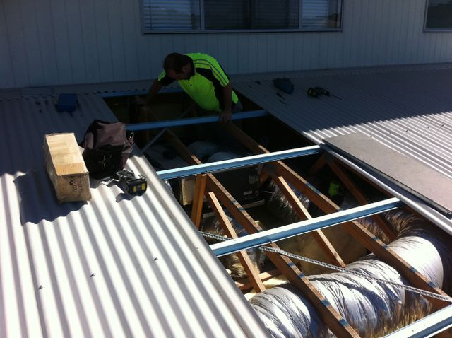 A man either reparing, installing and maintaining ducted air conditioning in the Gold Coast