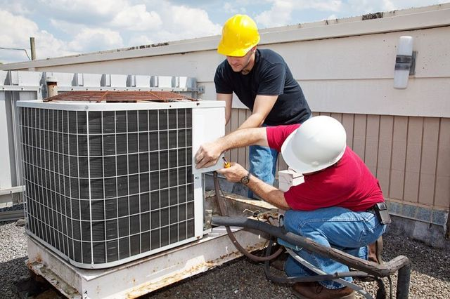 Two workers on the roof of a building fixing an air conditioning unit in Russellville