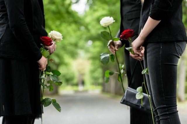 persone che reggono rose bianche e rosse