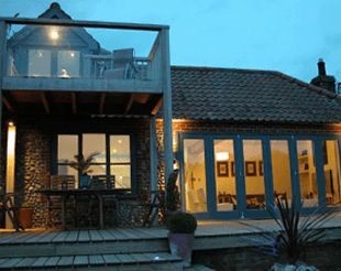 A converted bungalow at night with a glass front