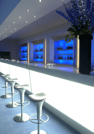 A long white bar with stools and spot lights above