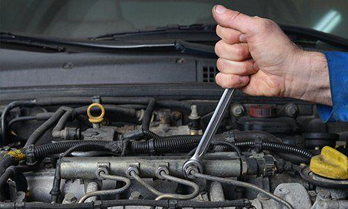 Impiegato stringe un bullone del motore auto