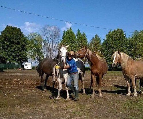 un uomo con un cappello da cowboy vicino a un cavallo