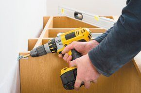 A man with a yellow drill, fitting some timber units