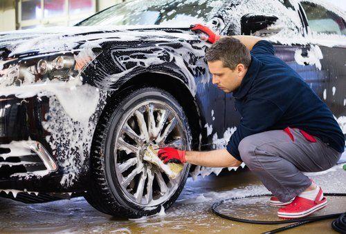 operaio mentre lavaggia una macchina