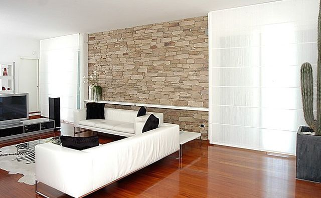 una sala con un pavimento in parquet e due divani di color bianco