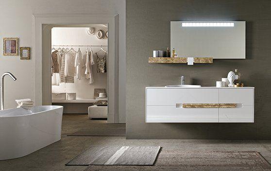 un bagno con una vasca e un lavabo con sopra uno specchio a muro