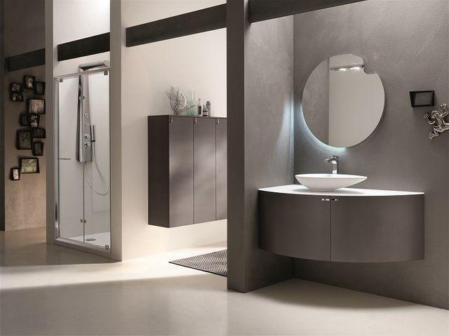 un bagno con muri e mobili di color grigio scuro e uno specchio rotondo a muro