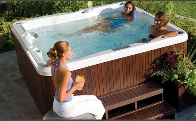 una vasca idromassaggio all'aperto con due persone dentro ed una donna seduta a bordo