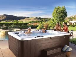una vasca idromassaggio con due persone dentro e altre due fuori che parlano