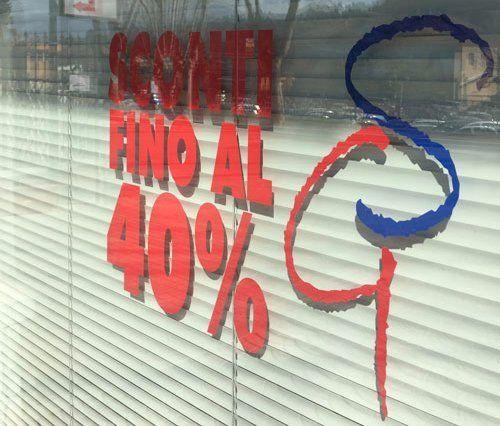 un adesivo su un vetro con scritto sconti fino al 40%