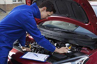 Auto mechanic examining a transmission in Lewiston, ME