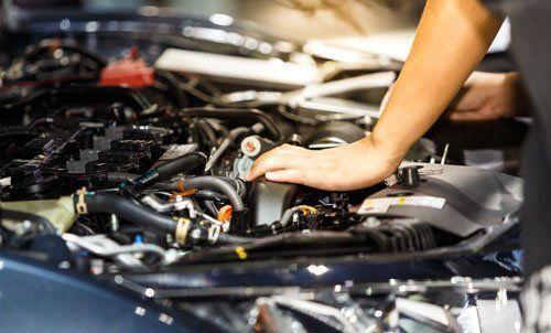Tecnico durante revisione motore auto