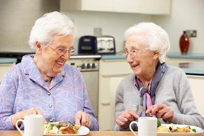 Two senior friends enjoying a meal together during winter in Greenville