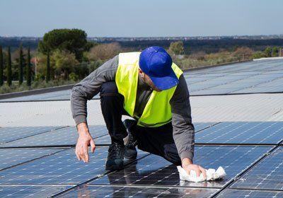 una persona che pulisce dei pannelli solari con uno straccio