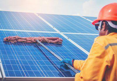 una persona che pulisce pannelli solari con un mocio
