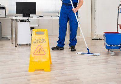 una perosna che pulisce a terra e un cartello giallo di sicurezza