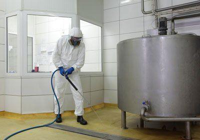 Un addetto con tuta protettiva che pulisce il pavimento
