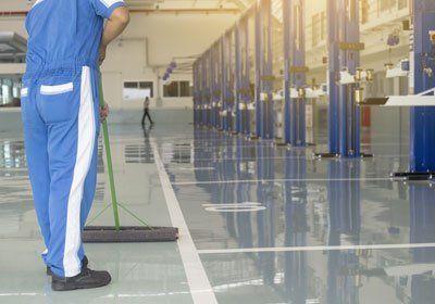 un addetto che pulisce il pavimento di un garage