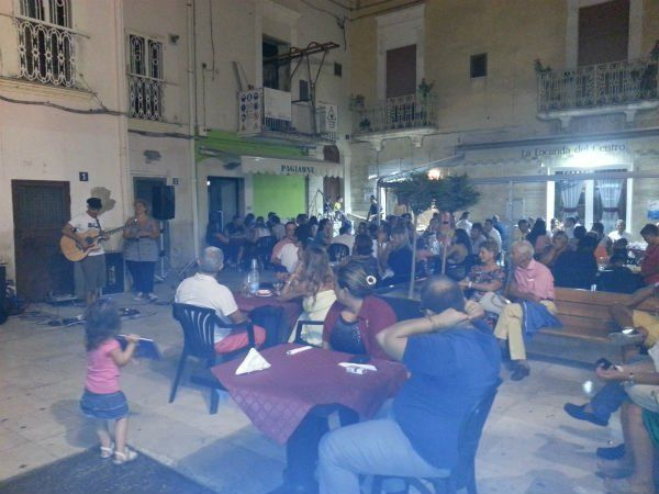 delle persone sedute ai tavoli fuori dalla pizzeria con delle persone che suonano