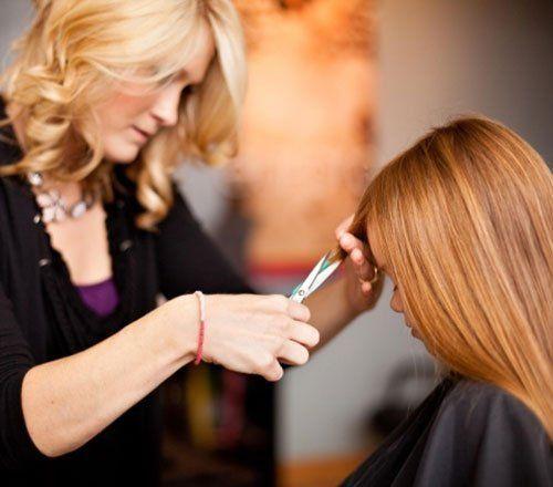 una Parrucchiera che taglia i capelli di una bimba