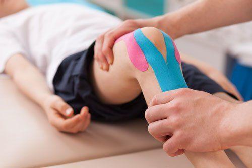 due mani che tengono un ginocchio ad un bambino durante la fisioterapia