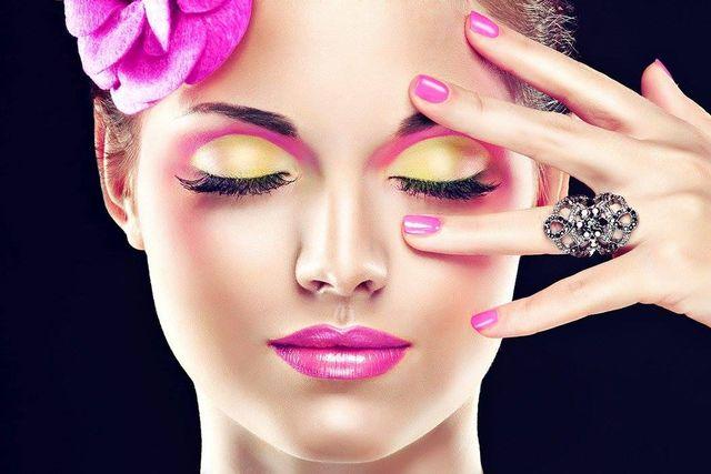 il viso di una donna truccata di color giallo e viola con un fiore in testa