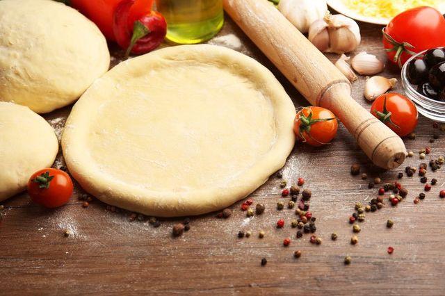 Piano di lavoro con impasti, mattarello, pomodorini ,aglio e pepe a Sarzana, SP
