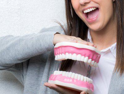 ragazza sorridente che mostra il modellino di una dentatura