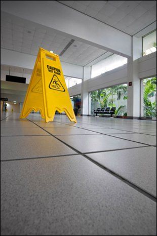 yellow warning board on a tiled floor with windows in the background
