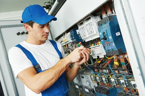 Electrician engineer screwing equipment in fuse box