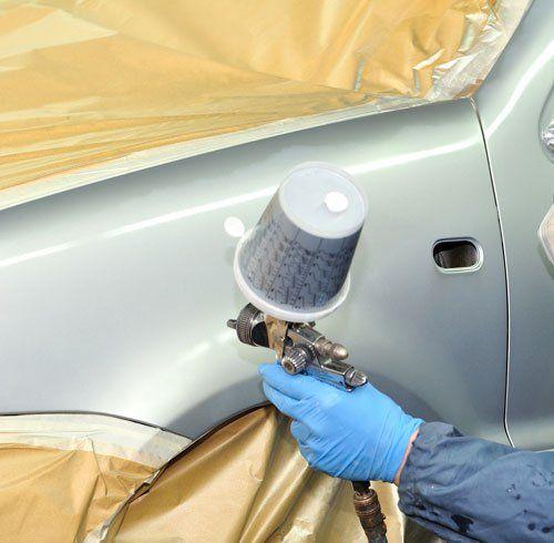 un uomo con un uniforme e una mascherina sta verniciando una vettura
