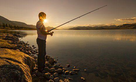 pescatore di fronte a un lago