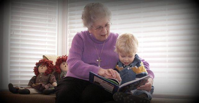 Elderly woman enjoys book with her grandson