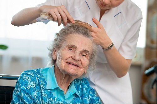 Caregiver brushes elderly client's hair