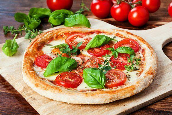 Pizza di pomodoro con un tocco di basil e mozzarella