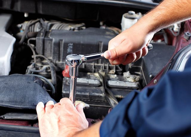 meccanico che ripara il motore di un auto