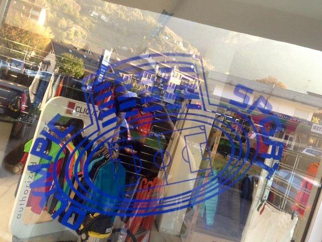 Logo della ditta sul vetro dellla vetrina, dalla quale si vedono i capi esposti