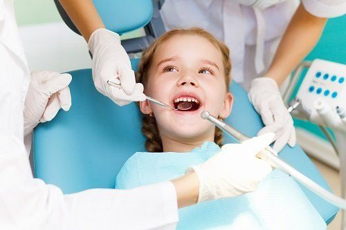 Dentisti che visitano bambina sdraiata sul lettino