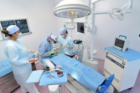 Equipe di chirurghi dentali mentre esegue un intervento su un paziente