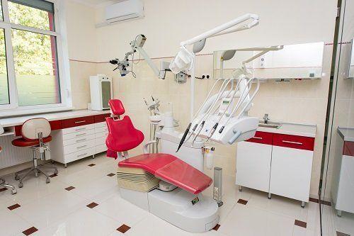 Sala di clinica dentale con lettino rosso e strumenti odontoiatrici