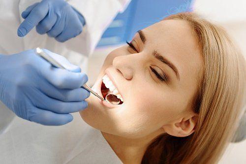 Dentista che visita il cavo orale di una donna bionda
