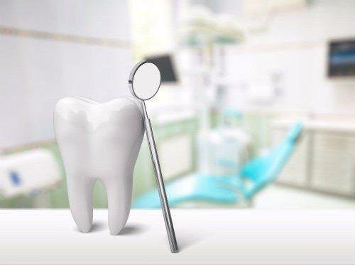 Specchio da dentista sostenuto da un modellino di dente