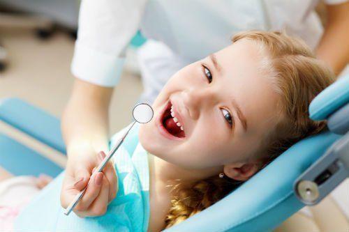 Bambina che sorride durante una visita dal dentista