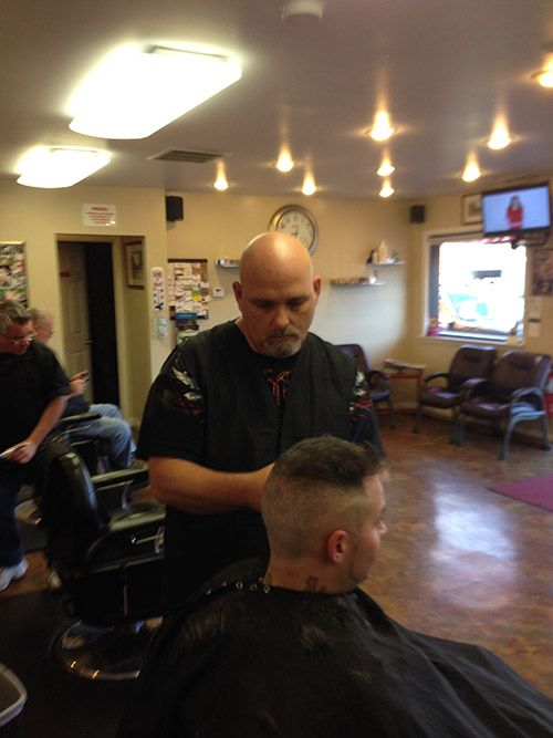 Danny, one of the professional barbers at Olde Milford Barber Shoppe, cutting a client's hair