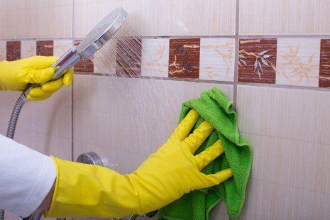 mani con guanti lava parete della doccia