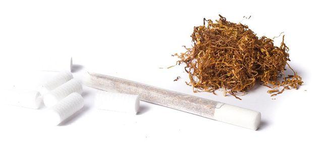 rolled cigarette next to isolated filters and tobacco